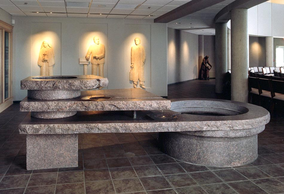 Just inside the main worship space is the three-tiered baptismal font made from eight tons of granite. Surrounding the font are six bas-relief modern witnesses to the baptismal ideals. On one side of the font are Mother Teresa of Calcutta (dedicated lover of the poor and neglected), Thomas Merton (Trappist monk and world-renowned writer), and Karl Rahner (influential Jesuit theologian). On the other side of the font are Martin Luther King, Jr. (civil rights leader), Therese of Lisieux (a Carmelite nun and Doctor of the Church), and Dorothy Day (lay peace and justice advocate and co-founder of the Catholic Worker Movement).